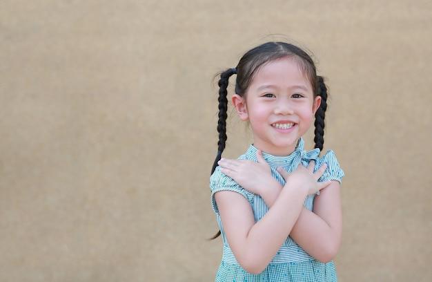 A expressão asiática pequena feliz da menina da criança cruza seus braço e sorriso. crianças confiantes e alegres.