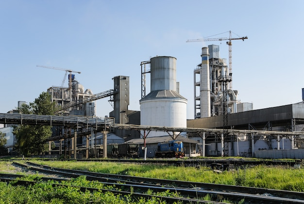 A fábrica de cimento em operação no fundo do céu azul