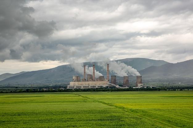 A fábrica faz as nuvens no campo verde