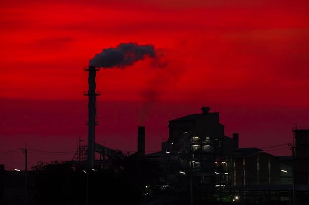 A fábrica liberou a chaminé de fumaça no pôr do sol o aquecimento global