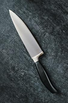 A faca de cozinha do chef está na diagonal em uma superfície escura