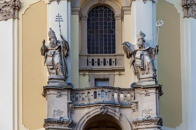 A fachada da velha igreja com esculturas de pedra dos santos em frente a uma porta de entrada.