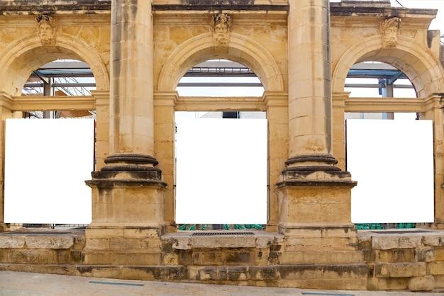 A fachada de um antigo edifício histórico com colunas e janelas em arco.