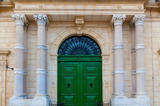 A fachada de um edifício histórico com grandes colunas de pedra e elementos decorativos