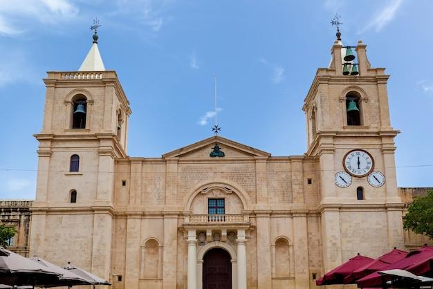 A fachada de uma co-catedral católica romana no fundo de um céu azul puro em valletta.