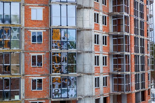 A fachada de vidro de apartamentos residenciais em um prédio alto janelas e varandas