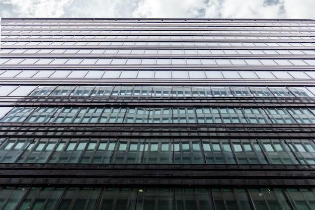 A fachada do prédio de escritórios tiro de baixo para cima com uma faixa horizontal de céu cinza com nuvens. as janelas do centro de negócios refletem o edifício adjacente