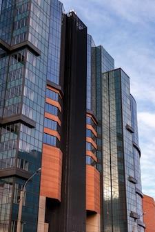 A fachada moderna do prédio de escritórios é um fragmento abstrato, com janelas brilhantes em estrutura de aço. excelente plano de fundo para um cartão de visita, folheto, banner com espaço para uma inscrição ou logotipo