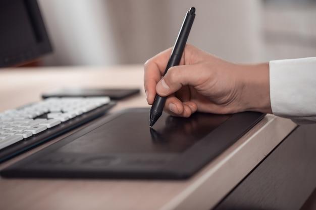 A falta de profundidade de campo do espaço de trabalho de um designer gráfico com uma caneta eletrônica, um computador.