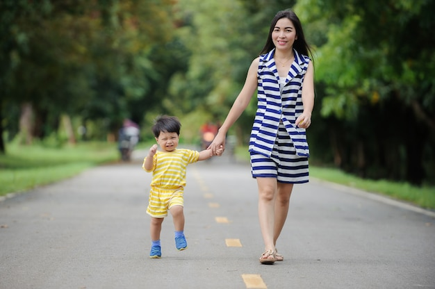 A família, a mãe feliz e o bebê que guardam as mãos que andam no parque, sentem felizes e relaxados.