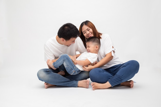 A família asiática alegre que senta-se sobre a parede branca se diverte pai que faz cócegas no filho pequeno. jovem casal com crianças vestindo jeans e top branco. os pais aproveitam o tempo livre jogando conceito