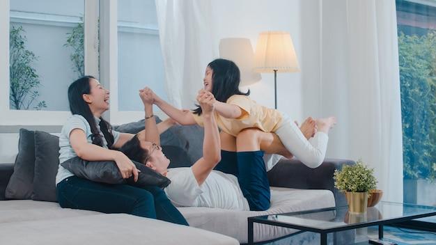 A família asiática nova feliz joga junto no sofá em casa. a filha chinesa do pai e da criança da mãe que aprecia feliz relaxa gastando o tempo junto na sala de visitas moderna na noite.