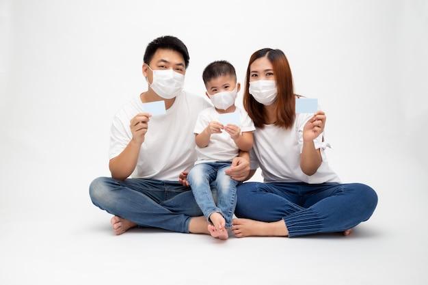 A família asiática que veste a máscara médica protetora para impede o vírus covid-19 e que mantém o cartão do cuidado do seguro isolado na parede branca. conceito de cartão médico de proteção familiar e seguro