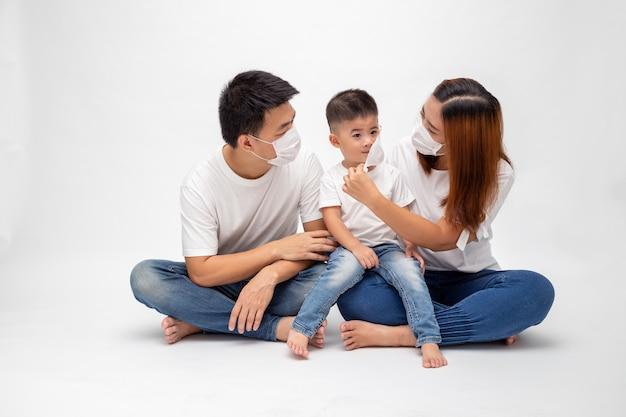 A família asiática que veste a máscara médica protetora para impede o vírus wuhan covid-19 e que senta-se junto na parede branca isolada assoalho. proteção da família contra o conceito de ar contaminado