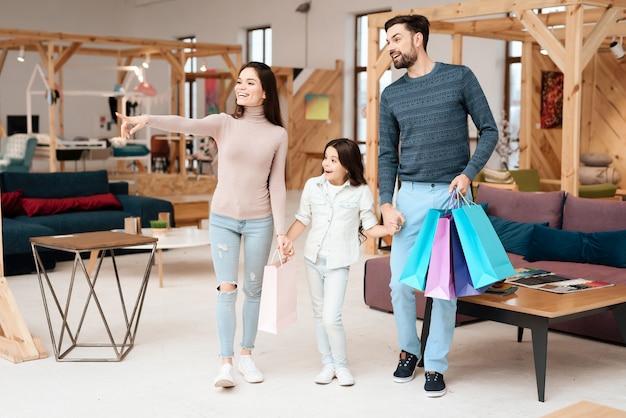 A família com menina está andando em torno da loja de móveis.