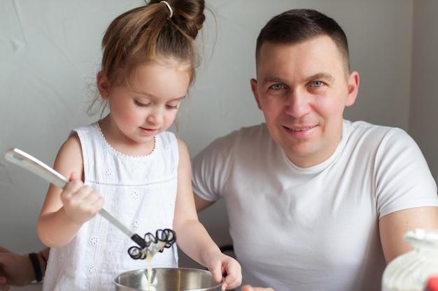 A família cozinha biscoitos na cozinha