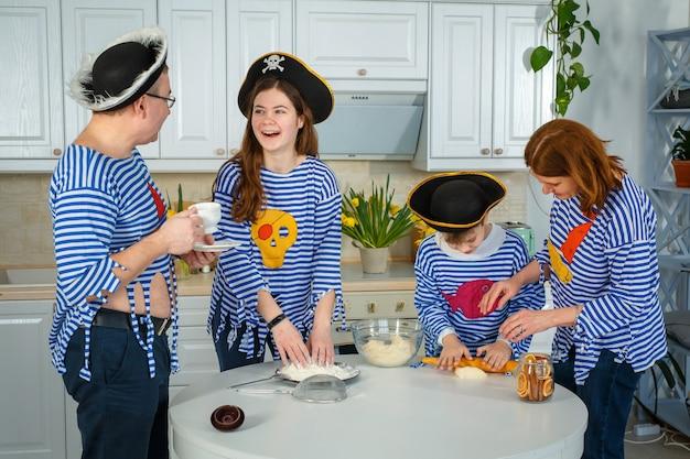 A família cozinha junta. marido, mulher e filhos na cozinha. família sove a massa com farinha. prepare a massa na cozinha.