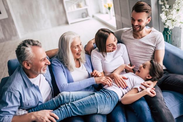 A família de várias gerações sentada no sofá