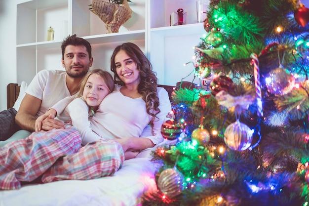 A família do sorriso estava deitada na cama perto da árvore de natal