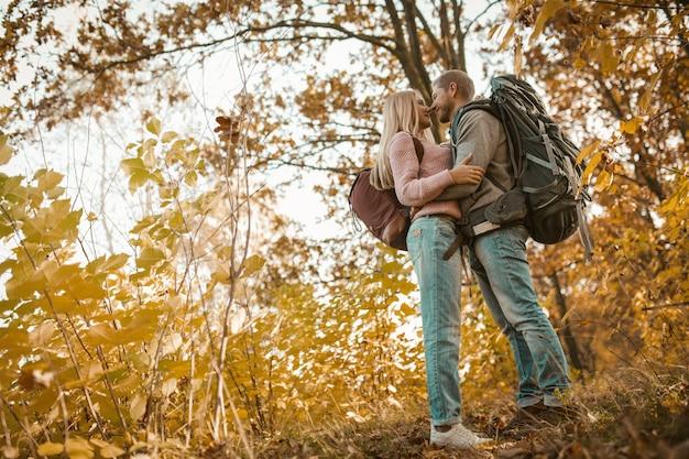 A família do viajante parou em uma floresta multicolorida de outono