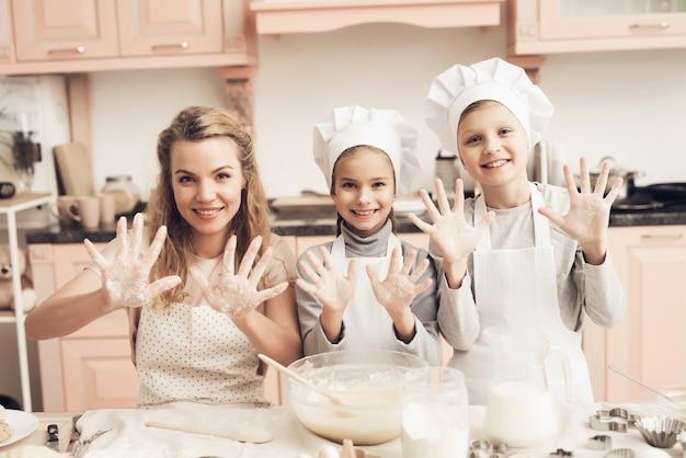A família doméstica do cozimento faz as mãos da massa na farinha.