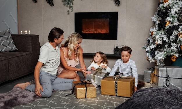 A família está comemorando o natal em casa, mamãe, papai e as crianças felizes abrindo presentes no ano novo