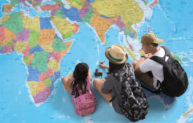A família está planejando uma viagem ao redor do mundo. eles estão olhando para um mapa do mundo
