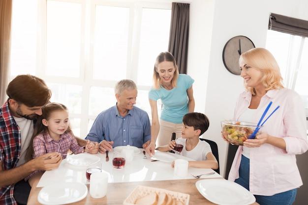 A família está sentada à mesa de jantar e se preparando para o jantar.