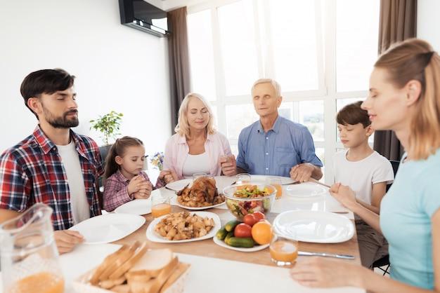 A família está sentada à mesa para o dia de ação de graças