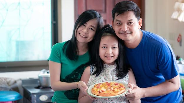 A família feliz consistia em pai, mãe e filha segurando bandejas de pizza caseiras na cozinha de casa