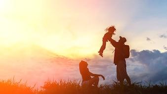A família feliz de três pessoas, mãe, pai e filho na frente de um céu do por do sol.