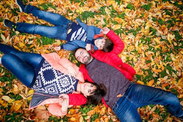 A família feliz encontra-se em uma grama nas folhas amarelas do outono.