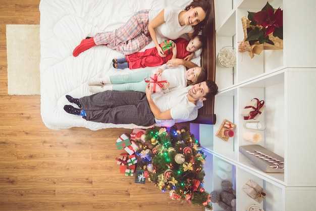 A família feliz estava deitada em uma cama perto da árvore de natal. vista de cima