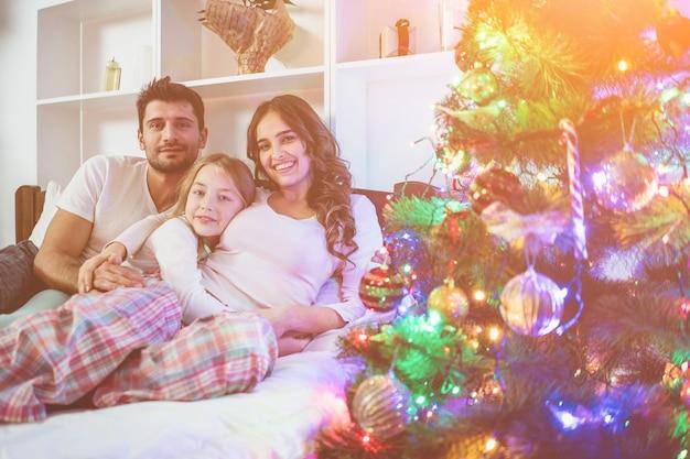 A família feliz estava deitada na cama perto da árvore de natal