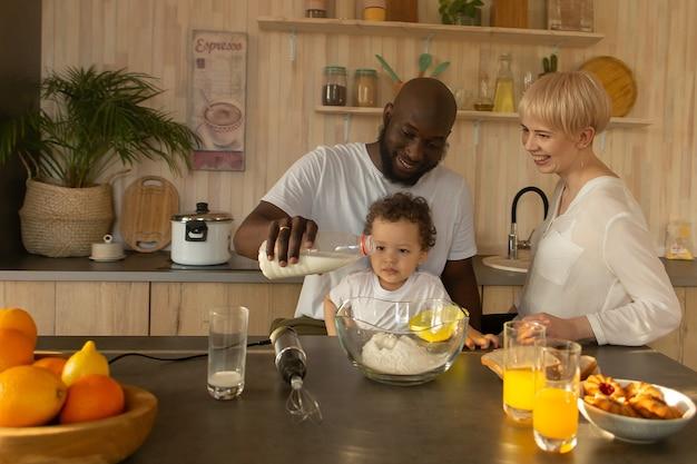 A família feliz no jantar em casa, multinacional