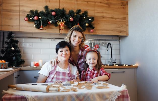 A família na cozinha se prepara para o natal e se diverte fazendo biscoitos.