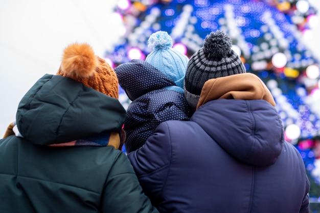 A família olha para a árvore de natal na feira. eles viram as costas para a câmera e vemos uma silhueta da família: mãe, pai e seu bebê