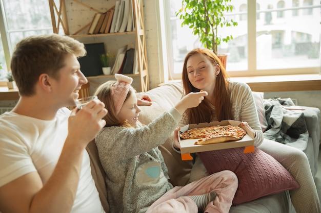 A família que passa o tempo agradável junto em casa, parece feliz e alegre