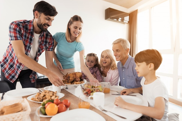 A família senta-se para jantar no dia de ação de graças.