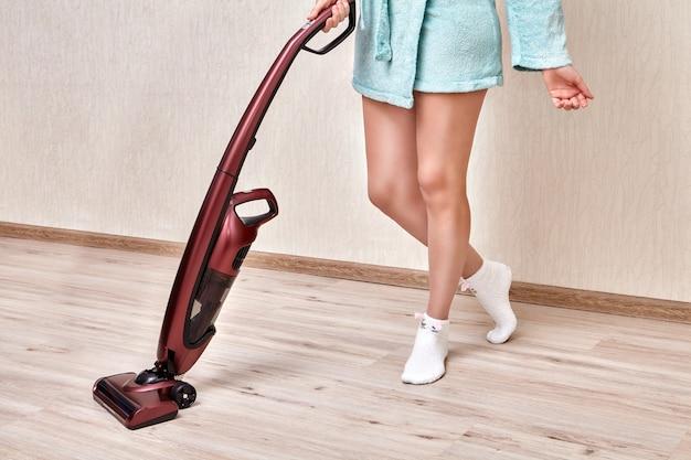 A faxineira de roupão azul limpa a poeira no quarto com aspirador de mão sem fio.