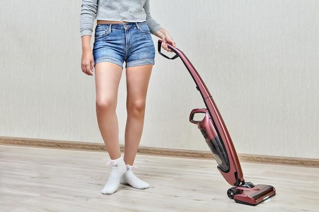 A faxineira de short jeans está fazendo a limpeza doméstica com a ajuda de um moderno aspirador de mão com luzes led acesas.
