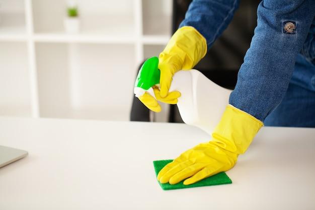 A faxineira faz a limpeza no escritório com um pano úmido.