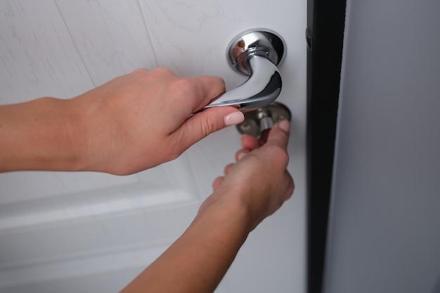 A fechadura da porta é aberta pela mão de uma mulher, close-up