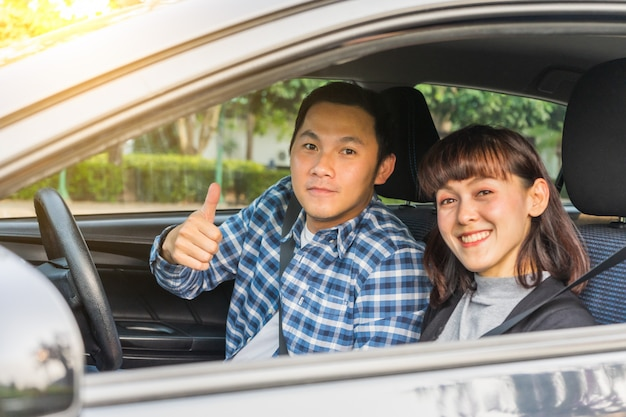 A felicidade asiática nova dos pares que senta-se na feira automóvel manuseia acima. conceito de viagens, primeiro conceito de seguro de segurança, novo conceito de carro
