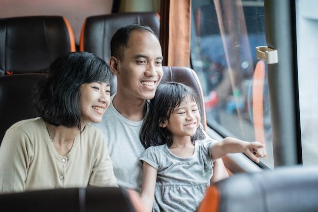 A felicidade de uma menina com o dedo apontando para o colo dos pais enquanto se senta no banco do ônibus durante a viagem