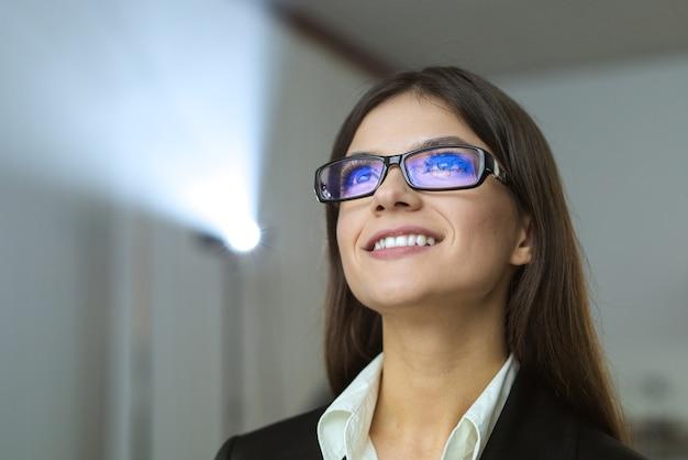 A feliz empresária com óculos no fundo do projetor