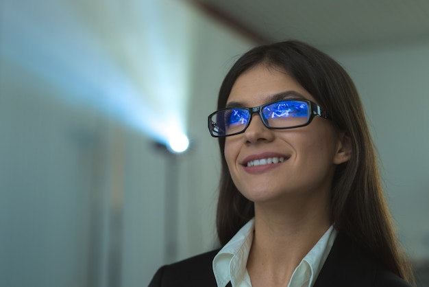 A feliz empresária de óculos no contexto do projetor