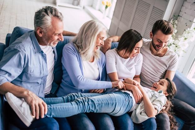A feliz família de várias gerações sentada no sofá