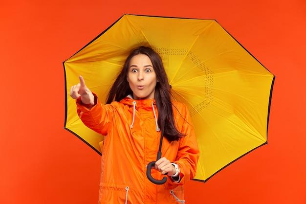 A feliz sorridente jovem posando no estúdio com casaco laranja outono e apontando para a esquerda isolada no vermelho. emoções positivas humanas. conceito de clima frio. conceitos de moda feminina