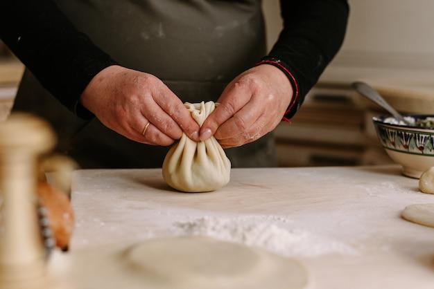 A fêmea adulta cozinha em um avental envolve a carne picada na massa. uma mulher está cozinhando khinkali e beliscar a massa